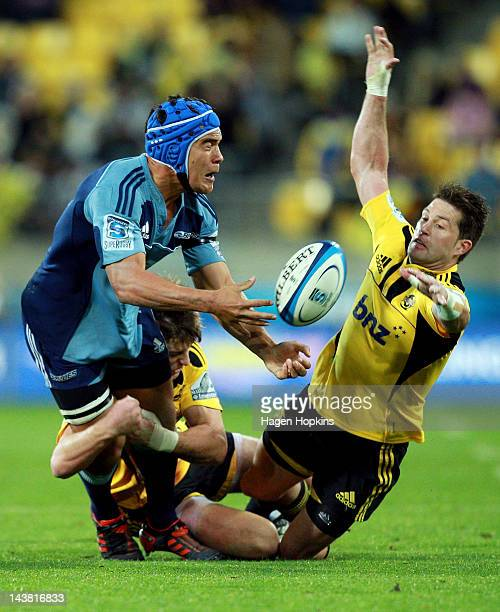 Benson Stanley of the Blues is tackled by Beauden Barrett of the Hurricanes while Cory Jane attempts an intercept during the round 11 Super Rugby...