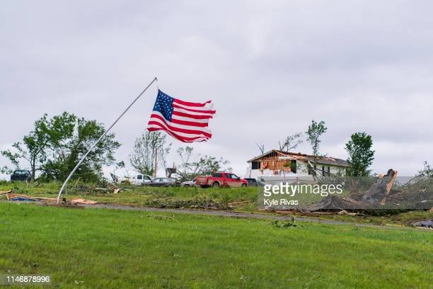 A bent American flag pole waves as homes sit heavily damage after a tornado devastated the area the night before on May 29 2019 in Linwood Kansas The...