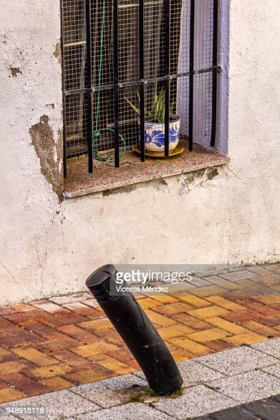 bent bollard and window with flower pot - bollard stock photos and pictures