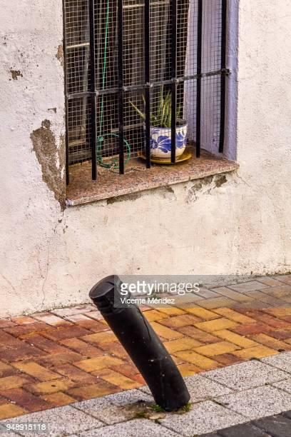 Bent bollard and window with flower pot