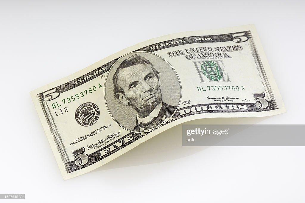 Curvada billete de cinco dólares estadounidense : Foto de stock