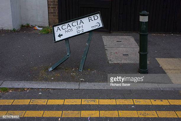 A bent street sign for Acacia Road in Mitcham London borough of Merton Apparently damaged by a reversing vehicle in a side street of a south London...