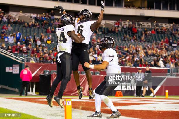 Bentavious Thompson of the UCF Knights celebrates with Marlon Williams and Dillon Gabriel after scoring a touchdown against the Temple Owls in the...