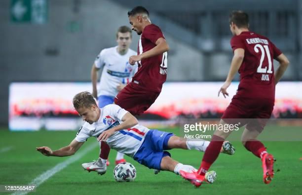 Bentley Bahn of Rostock is challenged by Kenny Redondo and Hendrick Zuck of Kaiserslautern during the 3. Liga match between 1. FC Kaiserslautern and...