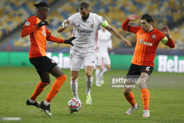 Benzema of Real Madrid in action against Taras Stepanenko and Vitao of Shakhtar during the UEFA Champions League group B football match between Real...