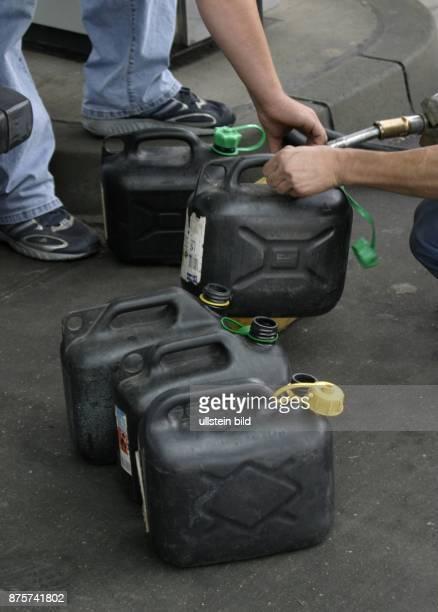 Benzin Benzinpreis Ölpreis Benzinknappheit Benzinvorräte Autofahrer füllen Benzinkanister an einer Tankstelle