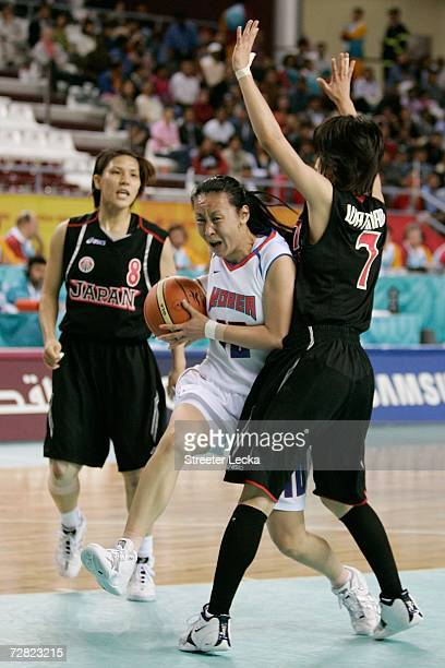 Beon Yeon Ha of the Republic of Korea drives against the defense of Yuka Watanabe and Noriko Sakaibara of Japan during the Women's Basketball Bronze...