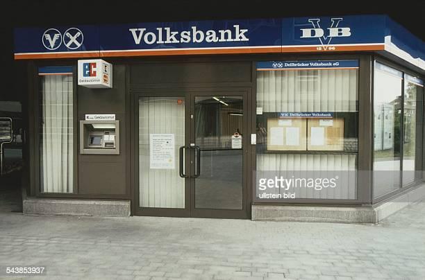 Über dem Eingang der Filiale der Dellbrücker Volksbank eG befinden sich Logo und Schriftzug der 'Volksbank' neben dem Eingang ein ecGeldautomat...