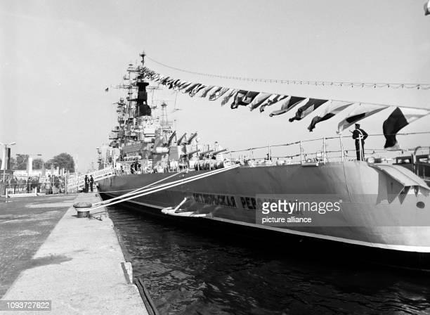 Über die Toppen geflaggt liegt das Schlachtschiff Oktjabrskaja Revoljuzia der sowjetischen Seekriegsflotte am an einem Kai im Rostocker Überseehafen...