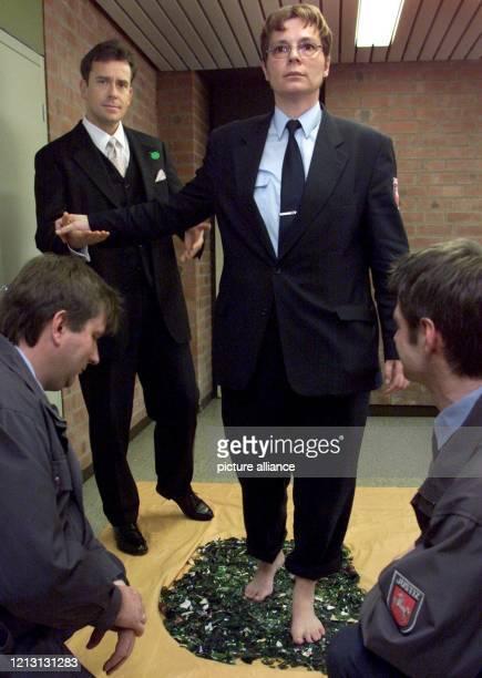 Über einen Scherbenhaufen geht Justizvollzugsbeamtin Katrin Wiechmann, geführt vom Motivationstrainer Jürgen Höller, am 16.3.2000 in der...