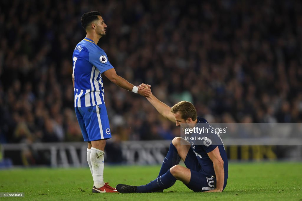 Beram Kayal of Brighton & Hove Albion helps Harry Kane of Tottenham Hotspur to his feet during the Premier League match between Brighton and Hove Albion and Tottenham Hotspur at Amex Stadium on April 17, 2018 in Brighton, England.