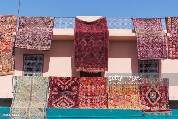 berber carpets on display in place (square) rahba kedima on sky  background marrakesh, morocco - berber photos et images de collection