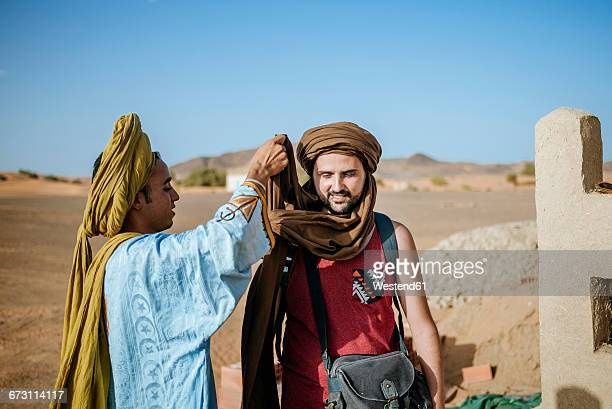 Berber guide helping touist wrapping a turban