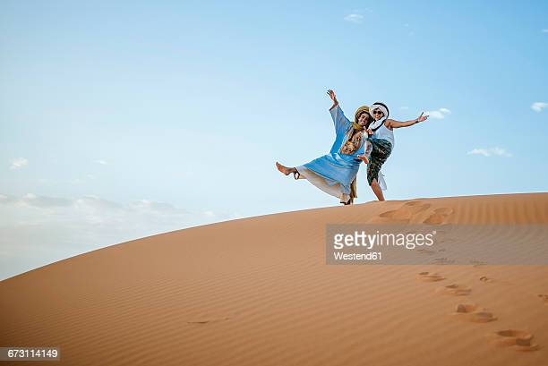 Berber man and woman tourist greeting in the desert