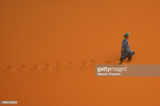 CONTENT] A berber man walks across desert dunes in the Sahara Erg Chebbi near Merzouga Morocco leaving footprints behind