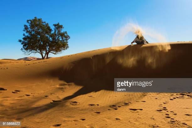 Berber playing and throwing with sands in Desert Sahara, creating angel with sands, Morocco