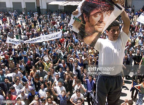 A Berber waves a poster of slain Kabyl singer Lounes Matoub as they demonstrate with more than 20000 people 28 May 2001 in Akbou some 65 km from...