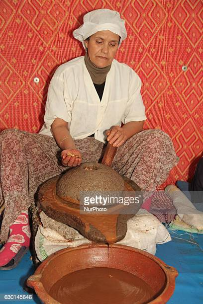 Berber woman uses a hand press to grind argan nuts and extract the oil at the argan oil cooperative in Morocco Africa on 17 December 2016 Argan oil...