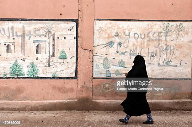 Berber woman wearing moroccan niqab passing by a nicely painted wall on the city center streets. Rissani, Ziz Valley, Morocco. 2013