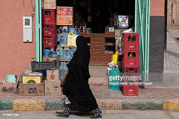 Berber woman wearing moroccan niqab passing by a shop on the city center streets. Rissani, Ziz Valley, Morocco. 2013