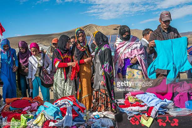 Berber women look through clothes for sale at the Imilchil Morocco Marriage and Betrothal Festival market