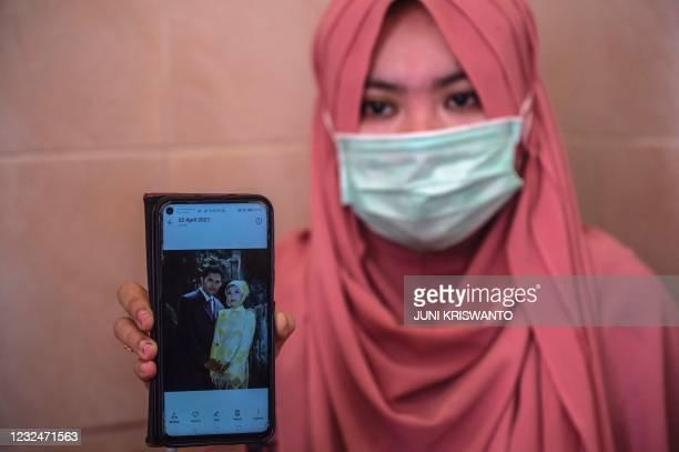 Berda Asmara shows a wedding photo with her sailor husband Mes Guntur Ari Prasetyo at their home in Surabaya on April 23 as the search continued for...