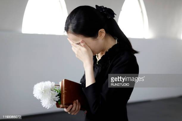 bereaved crying at funeral - mourning stock pictures, royalty-free photos & images