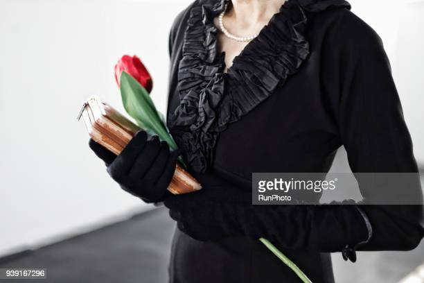 Bereaved holding red flower at funeral