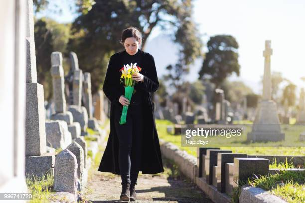 bereaved young woman in black taking flowers to grave - grief stock pictures, royalty-free photos & images