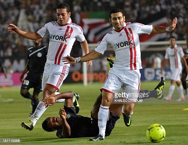 Berekum Chelsea's Bismark Idan falls after challenging Zamalek's Ahmed Samir and Hani Said during their CAF Champions League group B football match...