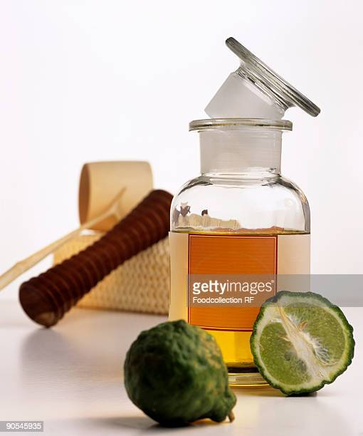 Bergamot oil in bottle, massage equipment and kaffir lime, close up