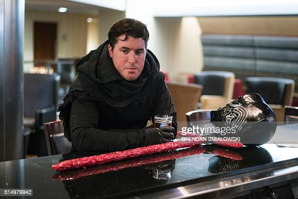 KJ Berger dressed as Star Wars character Kylo Ren has a beer at a hotel bar during the Cleveland Conocoction March 11 2016 in Cleveland Ohio / AFP /...