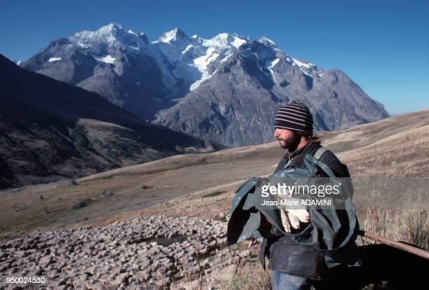 Berger tenant enveloppé un agneau pendant la transhumance face à la Meije Alpes France