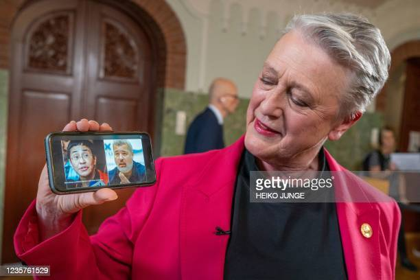 Berit Reiss-Andersen, chair of the Nobel Peace Prize Committee, presents a mobile phone displaying a combination of pictures of journalists Maria...