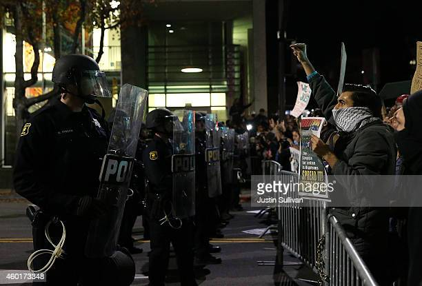 Berkeley police officers in riot gear line up in front of protetors during a demonstration on December 8 2014 in Berkeley California Protestors have...