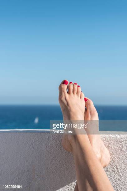 Überkreuzte Füße einer Frau mit rotem Nagellack auf weißer Mauer am Meer