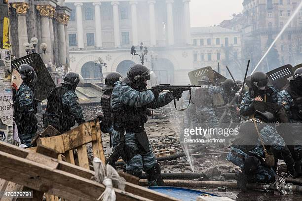 Berkut riot police shoot rubber bullets toward antigovernment protesters on Independence Square on February 19 2014 in Kiev Ukraine After several...