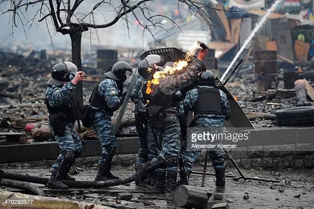 Berkut special forces of the Ukrainian police throw a Molotov cocktail during clashes with Antigovernment protesters on Independence Square in Kiev...