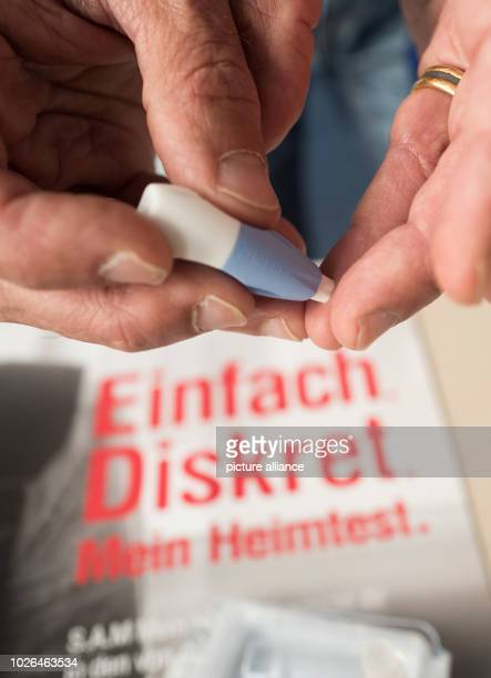 A man takes a blood sample in a home test in order to additionally have himself anonymously examined for venereal diseases with a urine sample and a...