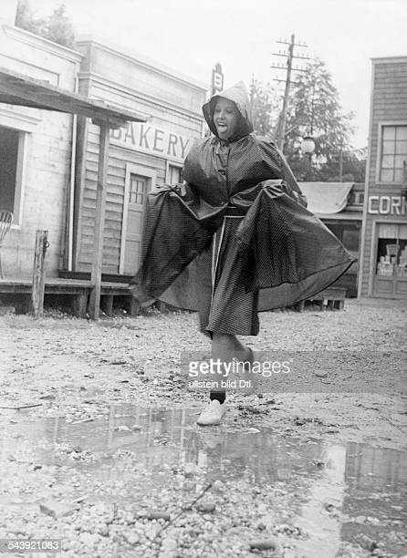 USA Berlin Berlin Rainy weather Woman with a raincoat in a unpaved street of an american village undated Published by 'Der Stern' 28/1939Vintage...