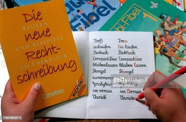 Blick in ein Schulheft mit der alten und neuen Schreibweise verschiedener deutscher Wörter und ein Nachschlagewerk mit den Regeln für die neue...