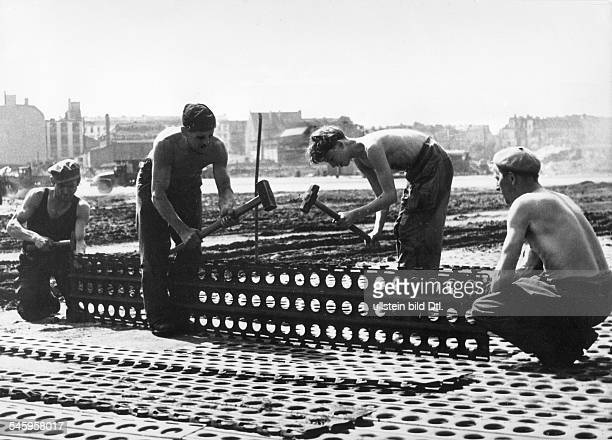 Berlin Blockade Contruction of a 2km long, second taxiway for supply planes at Tempelhof Airport. Shown: laying steel mats in order to adjust the...