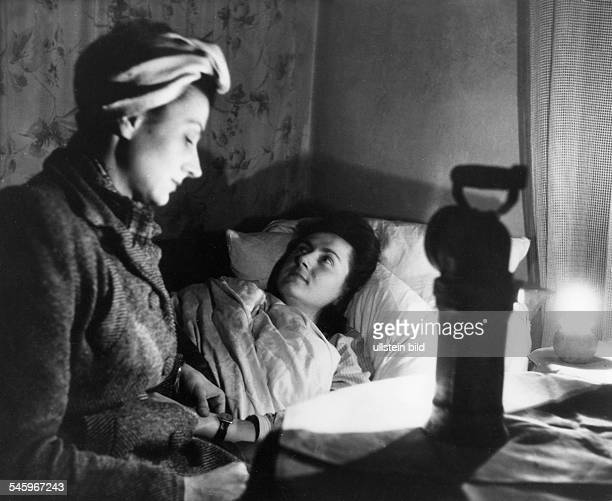 Berlin Blockade Woman doctor at a patient during the power cut-off. Medical treatment by candlelight - Photograph: Eschen, Fritz