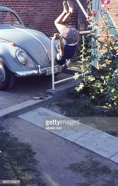 Berlin ca. 1955, Kind beim Spielen vor einem VW Käfer