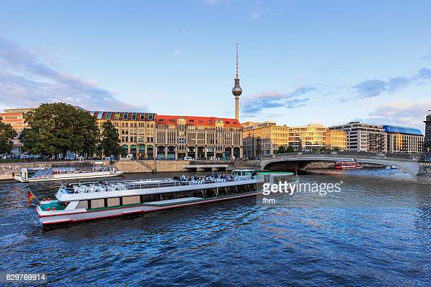 Berlin city with passing tourist boat and TV-Tower near Spree river (Berlin, Germany)