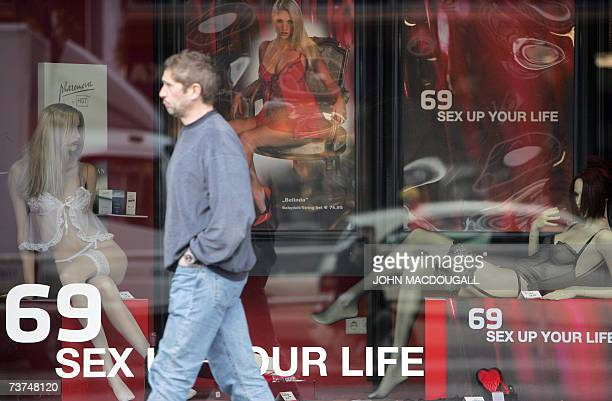 A man walks past a window advertising erotic items by German sex store giant Beate Uhse in Berlin 30 March 2007 Beate Uhse is trying to shed its...
