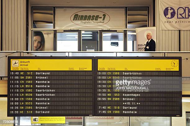Restaurant employee waits for customers behind a schedule board at Berlin's Tempelhof airport 09 November 2006. The airport, originally built in...