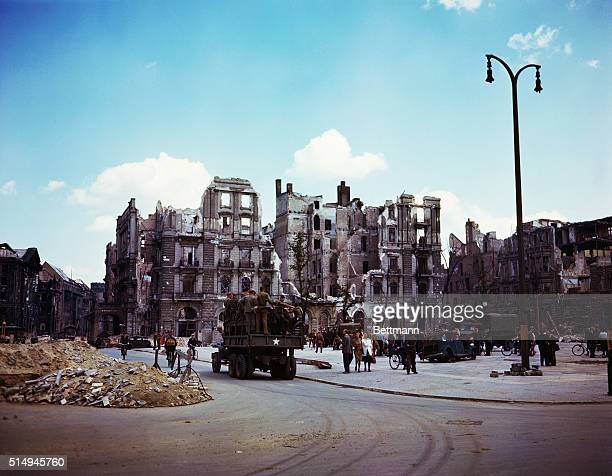 A Russian Army truck carrying troops down a street lined with ruined buildings rubble and crowds of civilians Several civilians can also be seen...