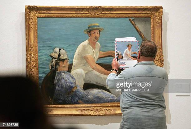A visitor compares the catalogue picture by French artist Edouard Manet to the original 'Boating' during the presentation to the press of the...
