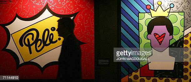 A visitor walks past paintings inspired by the life and achievements of Brazilian football legend Pele at an exhibition dedicated to his career in...